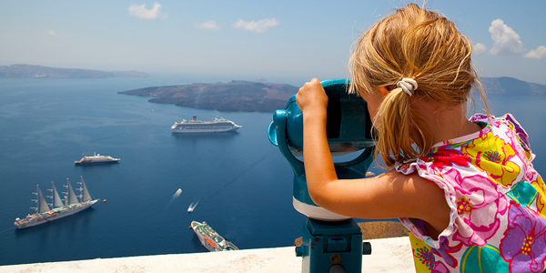 Girl looking at cruise ships with binoculars in Thira Santorini Greece