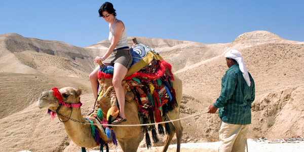 WOMAN ON A CAMEL IN THE JUDAEAN DESERT